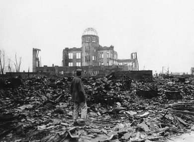 An Allied war correspondent stands amid the ruins of Hiroshima, Japan in 1945