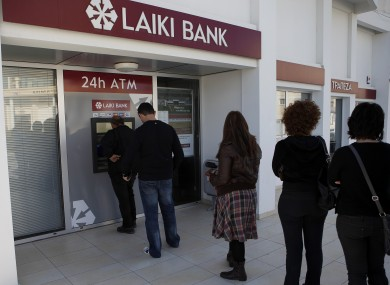 People queue to use an ATM machine outside of a Laiki Bank branch in Larnaca, Cyprus after hearing news of the bailout deal which involves a levy on their deposits.