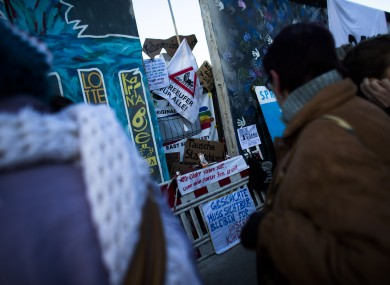 Protesters stand around a poster-covered hole in the East Side Gallery section of the former Berlin Wall in Berlin