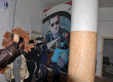 People tearing down a huge poster of President Bashar Assad and hitting it with their shoes in Raqqa which has been seized by rebel forces