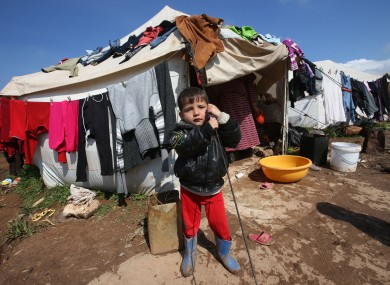 A Syrian refugee boy stands outside his tent at Atmeh refugee camp, in the northern Syrian province of Idlib.