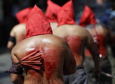 Filipino hooded penitents flagellate themselves during Holy Thursday rituals to atone for sins and mark the death of Jesus Christ.