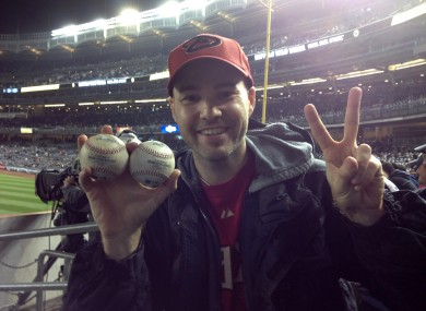 Zack Hample, a 35-year-old New Yorker holds the two balls he caught in the right-field seats.