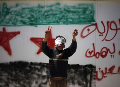 A 10-year-old Syrian refugee makes a victory sign in front of a wall at Zaatari refugee camp in Jordan