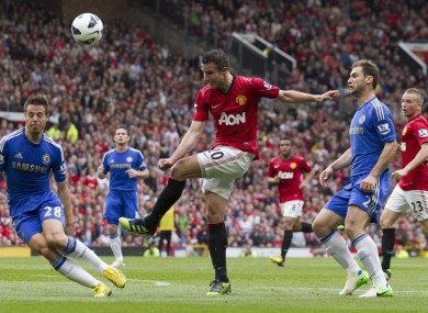 Manchester United's Robin van Persie, centre, fires the ball against Chelsea's Cesar Azpilicueta, left, as Chelsea's Branislav Ivanovic, second right, looks on during their English Premier League soccer match.