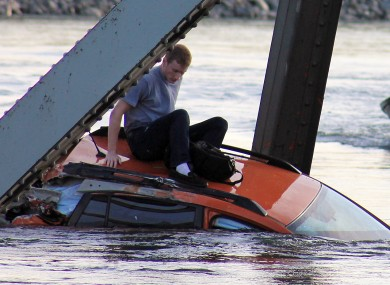 In this photo provided by Francisco Rodriguez, Bryce Kenning sits atop his car that fell into the Skagit River after the collapse of the Interstate 5 bridge there minutes earlier.