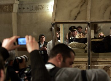 Pilgrims photograph the body of Padre Pio lying in repose inside a casket in a church in Italy in 2008
