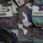 A young soldier with the last name of Jara stands guard at the entrance of the indoor stadium Estadio Victor Jara moments before it opens its doors to the homeless for the night during the winter season in Santiago, Chile.  (AP Photo/Brittany Peterson)