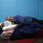 Armando Patricio Galleguillos Luna, 63, lies on a mattress in the designated area for people who have been using a substance, before they can access the rest of the shelter at the indoor stadium Estadio Victor Jara in Santiago, Chile. A census for the homeless shows that 12,225 people were living on the street last year. (AP Photo/Brittany Peterson)