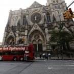 A sightseeing tour bus drives past the Cathedral Church of Saint John the Divine ahead of the funeral service for James Gandolfini in New York. (AP Photo/Mary Altaffer)