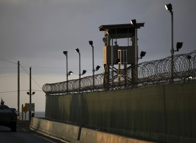A US trooper stands in the turret of a vehicle with a machine gun, left, as a guard looks out from a tower at the detention facility of Guantanamo Bay.