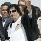 Libyan leader Moammar Gadhafi gives the peace sign as he arrives for a round table meeting at the G8 summit in L'Aquila, Italy on Friday, 10 July, 2009. (AP Photo/Michel Euler, Pool)
