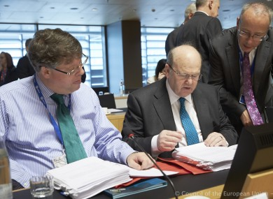 Michael Noonan speaks with officials before the beginning of this morning's meeting of EU finance ministers.
