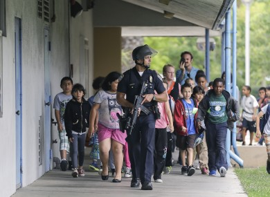 A police officer takes children to safety following the shootings.