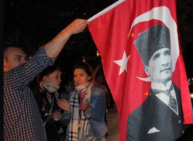 Thousands of people, some waving flags with posters of Turkey's founder Kemal Ataturk, gather in Ankara, Turkey