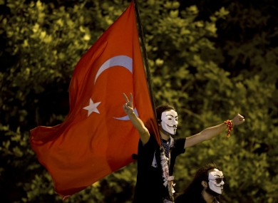 Protesters wearing Guy Fawkes masks hold a Turkish flag while standing on a barricade on a road leading to Taksim Square