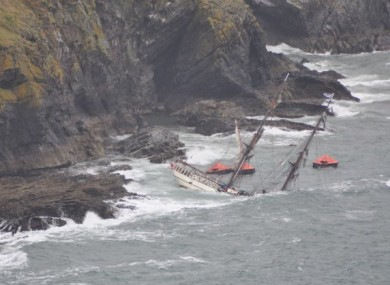The lifeboats from the ship are visible behind the stricken ship