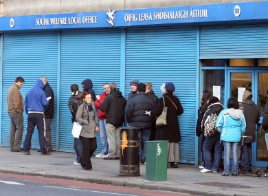 File pictures show people queuing at a Social Welfare office