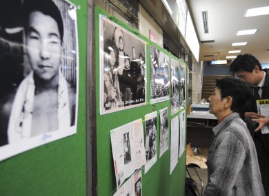 Hideko Hakamada, sister of death row inmate Iwao Hakamada,looking at family photos in 2008 during a campaign to have him freed. Iwao is in the pic on left.