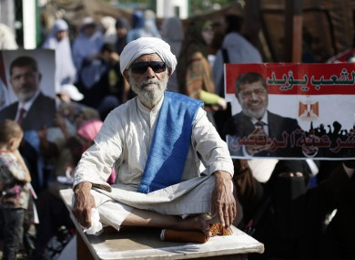 A supporter of Egypt's Islamist President Mohammed Morsi sits in front a poster with Arabic that reads,