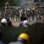 Egyptian army stand guard around the Republican Guard building in Cairo (AP Photo/Khalil Hamra).