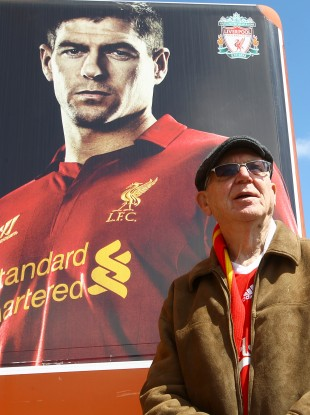 A liverpool fan stands in front of a Steven Gerrard poster on Merseyside.