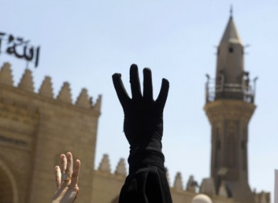 A supporter of Mohammed Morsi raises their hand in a recent protest calling for the reinstatement of the ousted President