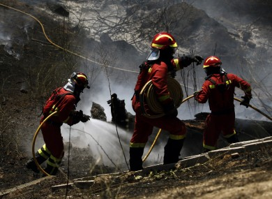 Firefighters carry fire hoses as they work to extinguish a forest fire outskirts of Cebreros, Spain, Sunday 4 August