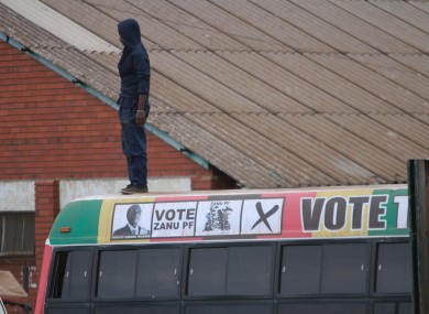 A man observes from on top of a campaign bus for President Robert Mugabe