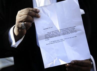 Bishop Gerald Seabrooks shows a statement made by Cathleen Alexis, mother of Washington Navy Yard gunman Aaron Alexis, in New York's Brooklyn borough on Wednesday