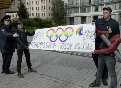 Russian police officers detain two gay rights activists holding a poster reading