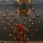 A Sikh devotee lights candles and lamps at the Golden Temple, Sikh's holiest shrine, illuminated on the occasion of the birth anniversary celebrations of Guru Ram Das in Amritsar, India. <span class=