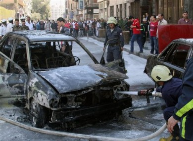 Firefighters extinguish a burning vehicle after two mortar rounds struck the Abu Roumaneh area in Damascus, Syria yesterday.