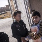 Twelve-year-old Abdo al-Fikri, left, arrives to school<span class=