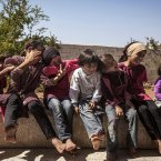 Children sit in front of their family's house in Madaya village.<span class=