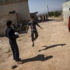 Syrian children play football outside their homes in Madaya village<span class=