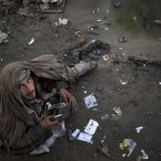 An Afghan drug addict smokes opium in a foul smelling river bed in the centre of Kabul. More than 1 million Afghans are addicts, living in squalor in its cities, sleeping on the street, in garbage-filled dried river beds reeking of human waste. <span class=