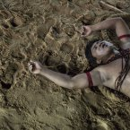 A victorious Surui Indian lies exhausted on the field of a tug of war competition during the indigenous games in Cuiaba, Brazi.<span class=