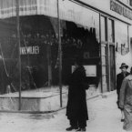 A pedestrian looks at the wreckage of a Jewish shop in Berlin.<span class=