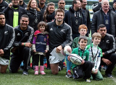 Irish children invade Richie McCaw's personal space.