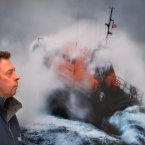 Photographer Nigel Millard looks at one of his pictures of a lifeboat heading out in stormy weather at the launch of the The Lifeboat: Courage on our Coasts photographic exhibition at Grand Canal dock in Dublin.<span class=