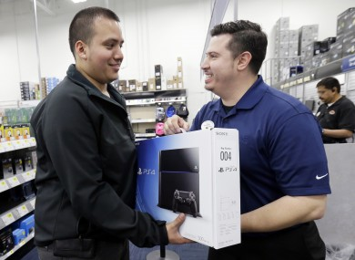 Andy Varadez, left, from Chicago, purchases a Sony PlayStation 4 from Best Buy sales manager Michael Centeno.