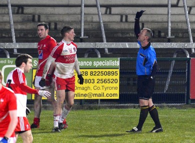 Derry's Declan Mullan becomes the first player to be shown the black card by referee Brendan Rice.