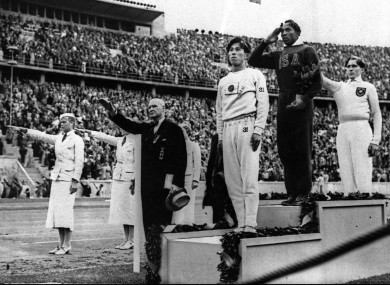 Jesse Owens salutes during the medal ceremony after he won Gold for the long jump. Germany's Lutz Long (right) gives the Nazi salute.