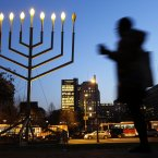 A woman passes a large menorah on Independence Mall on the seventh night of Hanukkah in Philadelphia. Hanukkah is the Jewish Festival of Lights, an eight-day commemoration of rededication of the Temple by the Maccabees after their victory over the Syrians. <span class=