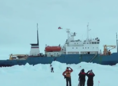 Passengers watch as a helicopter flies over the stranded ship