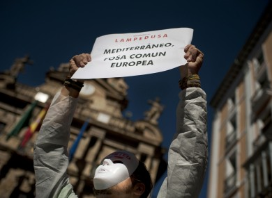 A demonstrator holds up a banner which reads,