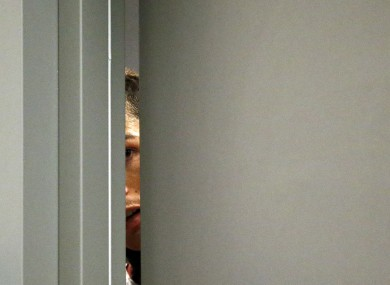 Cristiano Ronaldo takes a glimpse through a gap in the door during a press conference  before the Portugal-Sweden game.