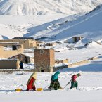 Afghan young women drag containers of water on the outskirts of capital Kabul, Afghanistan. <span class=