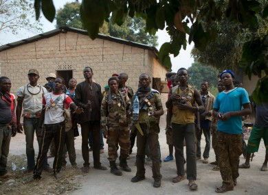 Anti-balaka militiamen stand together as they talk to journalists